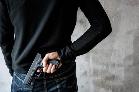 Achteraanzicht man bereikt handpistool bevestigd, diefstal, misdaad, ontvoering
