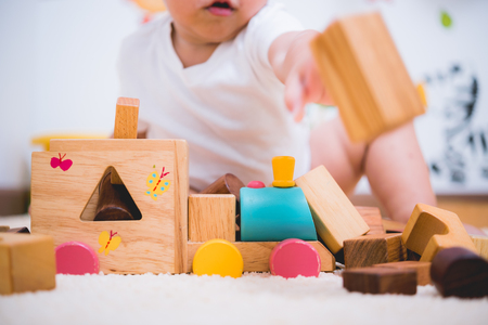 Asian child building playing toy blocks wood indoors room Banque d'images