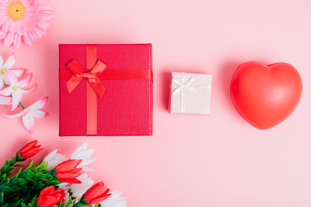 Red heart, flower and gift box on pink background with copy space, valentine day concept