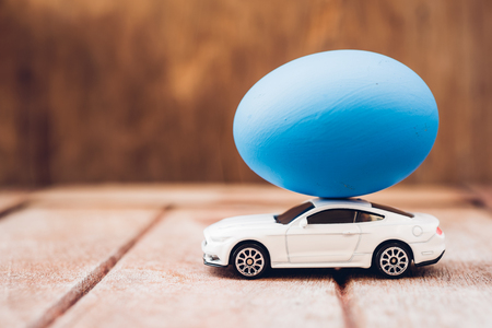 Easter egg and toy car on wooden background, happy easter day concept 写真素材