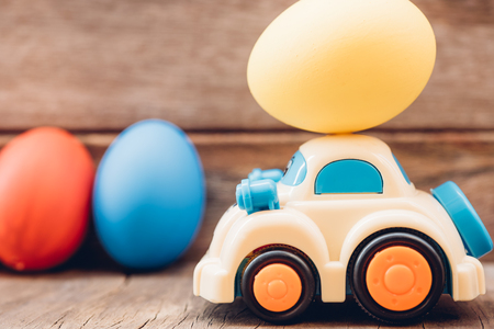 Easter egg and toy car on wooden background, happy easter day concept Stock Photo