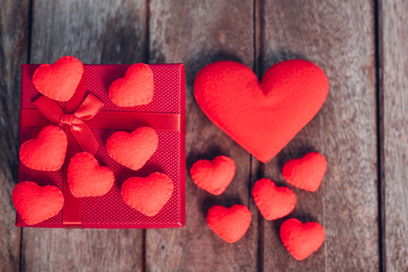 Fabric red heart and gift box on wooden background, valentine day concept