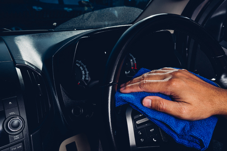 Worker man cleaning dust interior by cloth microfiber inside car after wash Stock Photo