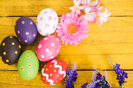 Vista superior de los huevos de Pascua sobre fondo de madera amarilla y tiene espacio de copia para su uso