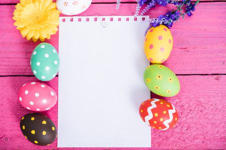 Vista dall'alto delle uova di Pasqua su sfondo di legno rosa e carta bianca per lo spazio di lavoro a bordo per l'uso