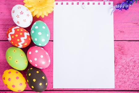 Widok z góry pisanki na różowym drewnianym tle i biały papier do użytku na tablicy