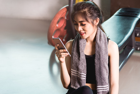 Woman girl healthy sitting using mobile smartphone after training exercise workout at lifestyle fitness gym