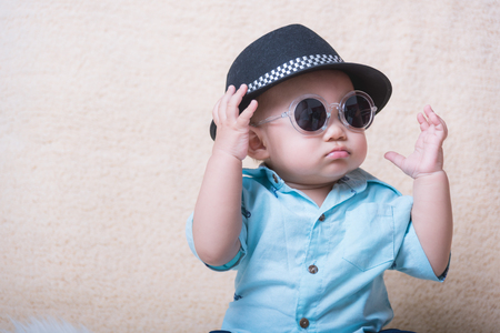 Baby child boy fashion sitting with sunglasses Imagens