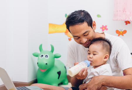 Father acting Mom feeding milk his son baby 1 year old while working on laptop computer in the home. 版權商用圖片