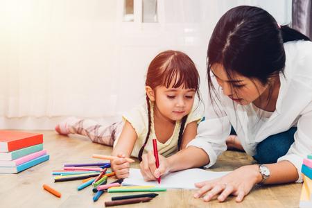 Familia feliz niño niño niña jardín de infantes dibujo maestro educación madre mamá con hermosa madre en casa habitación interior
