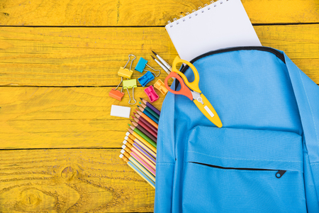 Top view Blue bag backpack for education children on yellow wooden  background back to school concept