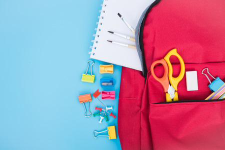 Top view Red bag backpack for education children on blue background back to school concept
