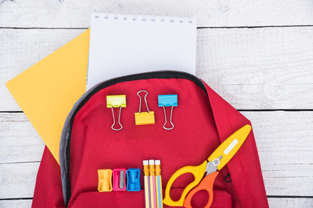 Top view Red bag backpack for education children on white wooden  background back to school concept