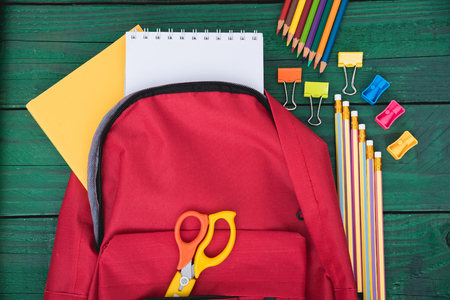 Top view Red bag backpack for education children on green wooden  background back to school concept Stock Photo