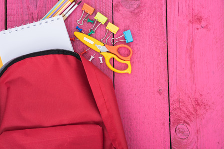 Top view Red bag backpack for education children on pink wooden  background back to school concept