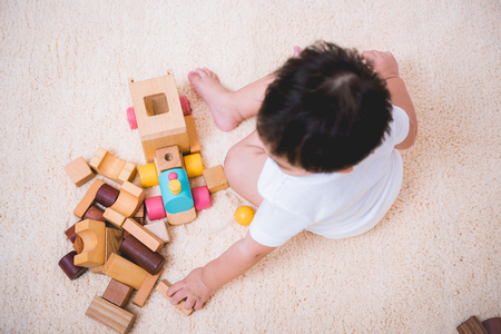 Vista superior del edificio del niño asiático jugando bloques de juguete de madera en el interior de la habitación