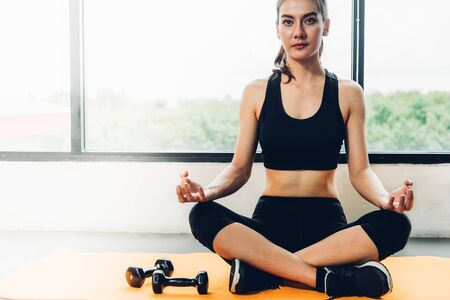 Beautiful woman sitting yoga on hands after exercise workout at fitness GYM