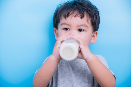 Asian little child boy about 2 year drinking milk from bottle glass itself on blue background