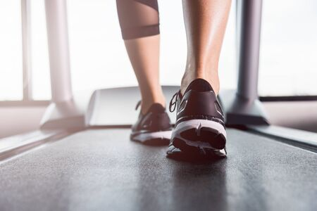 Feet of woman exercise workout running on treadmill at fitness gym