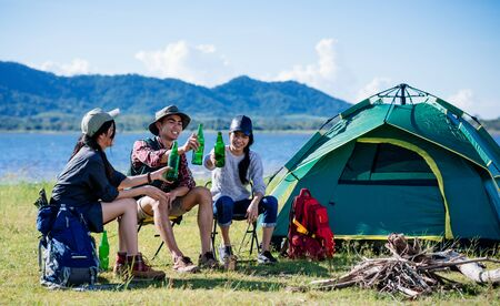 Camping camp in nature happy friends party and drinking beer together in summer at nature forest Фото со стока