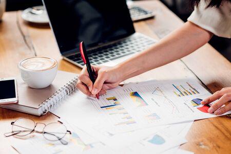 Mujer independiente de estilo de vida y computadora portátil examinó el docume de ganancias de gráfico en cafetería