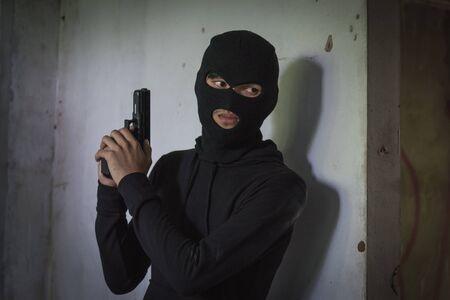 Hombre ladrón ladrón usar máscara sosteniendo pistola escondido armado esperando criminal