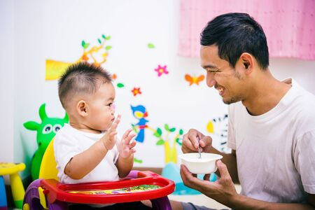 Father acting Mom feeding his son baby 1 year old on chair in the house