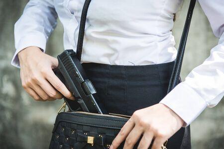 Młoda kobieta z ukrytą bronią w małej torebce
