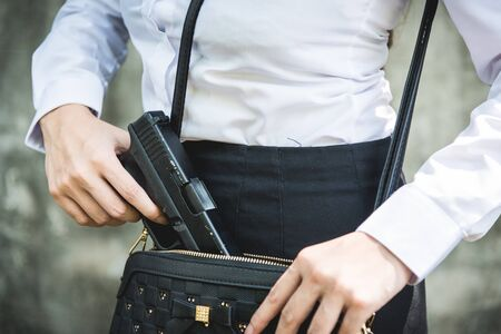 Young woman with concealed weapon gun in her small handbag Standard-Bild