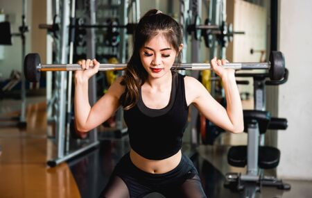 Young woman training barbell lifting exercise workout at fitness gym