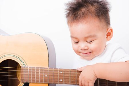 Asian portrait child boys 1 year 6 months playing guitar on white background