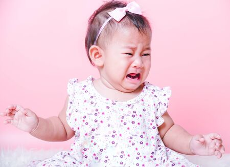 Asian girl baby face crying on pink background