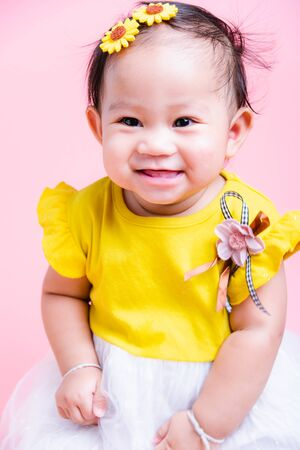 Close up portrait little baby girl in yellow beautiful dress she is smile in studio on pink background, Baby 8 months