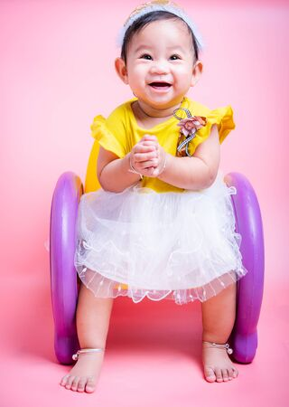 Asian princess little baby girl sitting on chair she is smile in studio on pink background, Baby 9 months Stock Photo
