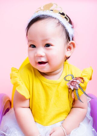 Close up face princess little baby girl in beautiful dress she is smile in studio on pink background, Baby 9 months Stock Photo