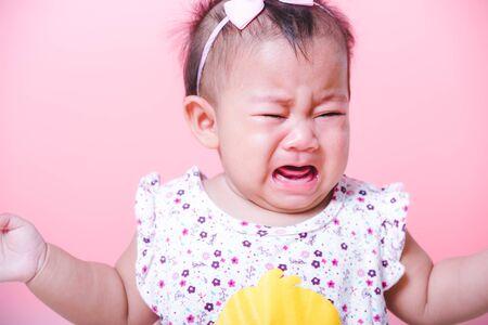 Cara de bebé niña asiática llorando sobre fondo rosa Foto de archivo