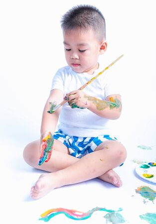 Happy asian baby childhood use paintbrush draw water color or fingerpaint on hand and arm by oneself, Baby 2-3 years