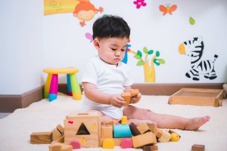 Child boy building playing toy blocks wood indoors room Stock fotó