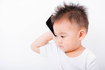 Asian portrait child boys 1 year 6 months calling with smartphone on white background 写真素材