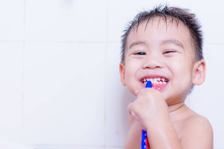 Asian kid brushes teeth with toothpaste on mouth every day after he shower