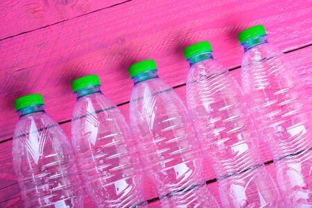Plastic bottles garbage recycling on pink wooden, environmental concept
