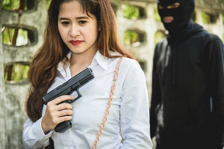 The black man robbers are about to criminal rob woman with a knife. But the woman fixes hide her gun in front of her.