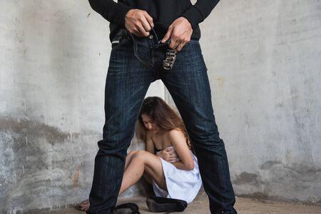 Hombre ladrón con pantalones después de la violencia violar a una mujer joven en una casa abandonada, concepto criminal de ladrón Foto de archivo