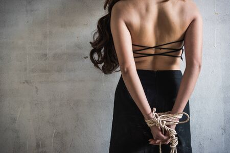 Young woman take off her shirt sexual raping rope tied arm standing facing wall, criminal robber concept with copy space