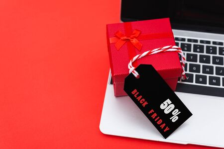 Online shopping, Promotion Black Friday Sale text on black tag with computer laptop and gift box on red background. Stock Photo