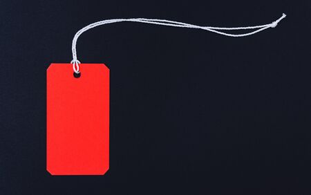 Red tag label on black background, blank copy space for you work