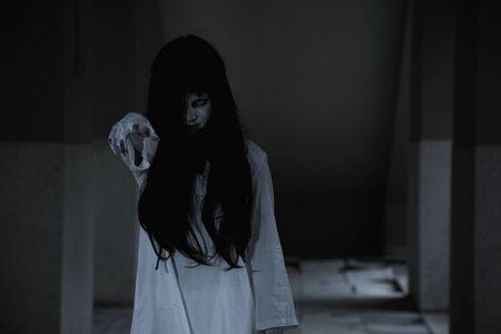 L'horreur fantôme de femme souligne du doigt à l'obscurité, concept de jour d'halloween Banque d'images