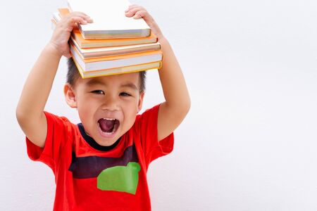 Back to school, Asian student boy kid stack book balanced on head and on white wall background, Education concept