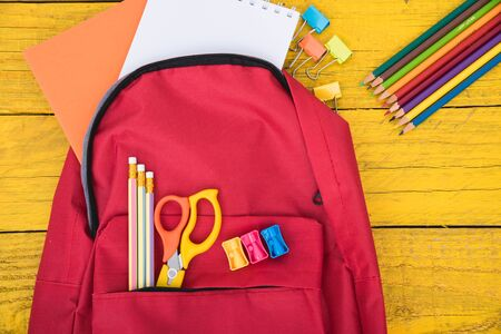 Top view Red bag backpack for education children on yellow wooden  background back to school concept
