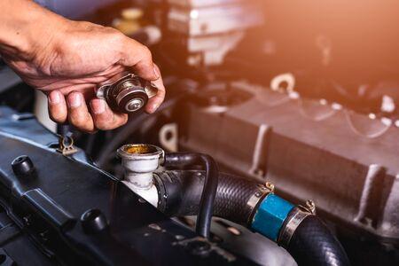 La mano del servicio técnico mecánico de automóviles compruebe el agua de refrigeración que abre la tapa del radiador en el garaje